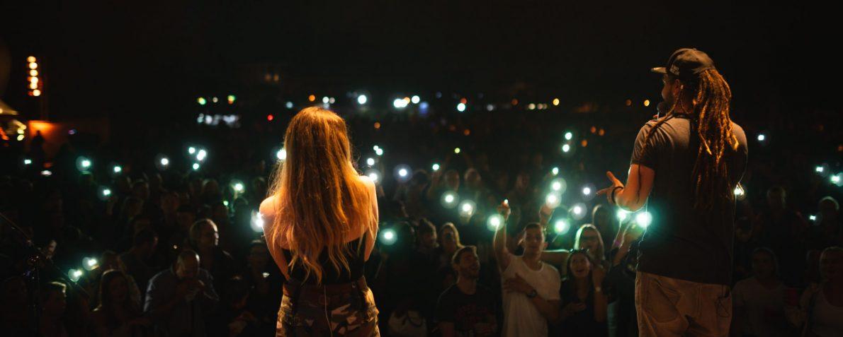 Sänger und Sängerin einer Partyband die man auch als Liveband Mannheim mieten kann, stehen vor großem Publikum