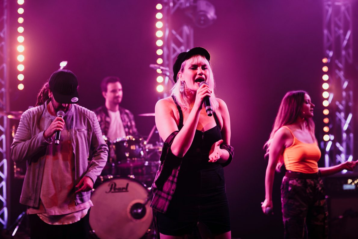 Sängerin performt auf Bühne mit dem Mikrofon in der rechten Hand während drei Mitmusiker im Hintergrund tanzen