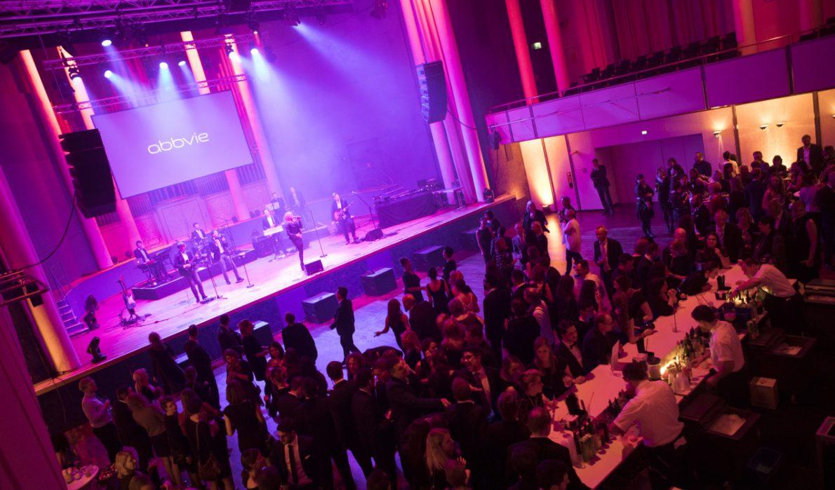Liveband mieten für Firmenevent vor feiernden Gästen auf großer Saalbühne