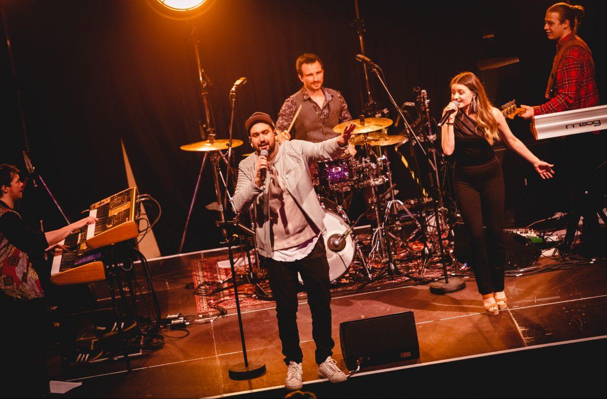 Coverband und Partyband aus Mannheim steht auf einer beleuchteten Bühne auf einem Firmenevent im Rosengarten Mannheim und performt Covermusik